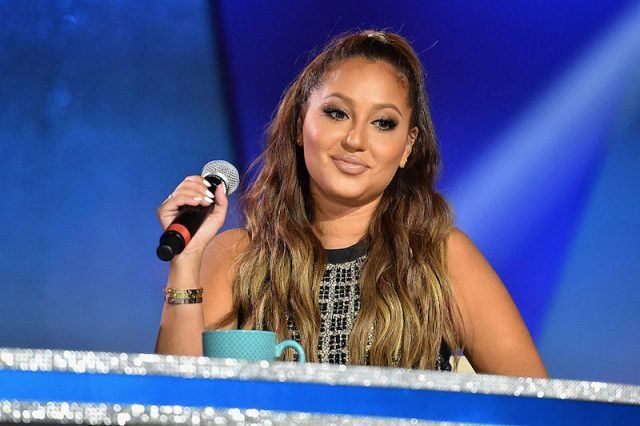 Adrienne Bailon smiles and holds up a microphone.