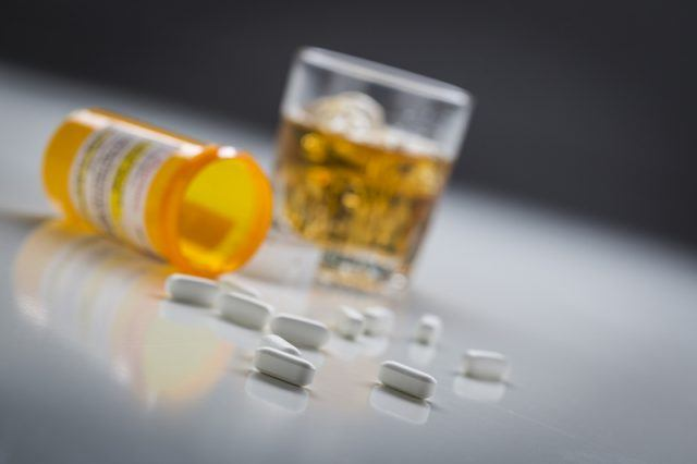 A glass of alcohol and a container of pills.
