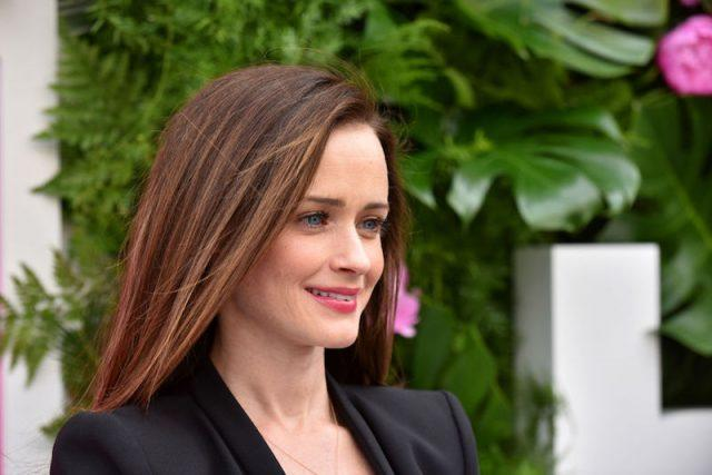 Alexis Bledel smiling while posing outdoors.