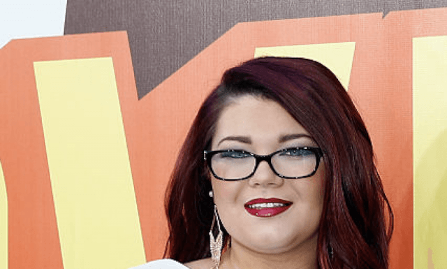 Amber Portwood smiles while wearing glasses.