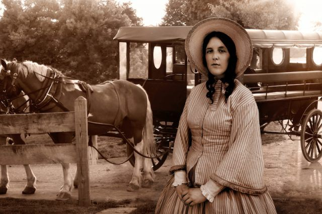 An Amish woman stands in front of a horse and carriage.