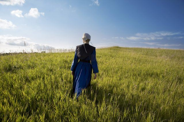 An amish woman standing in a field.