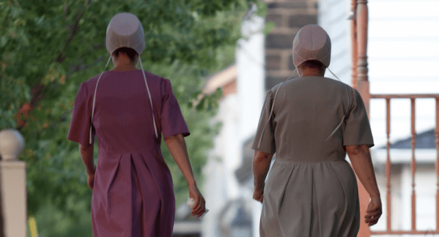 Two women walking together down a street.