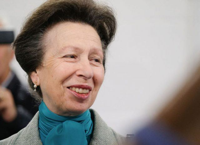Anne, Princess Royal smiles while wearing a suit and blue scarf.