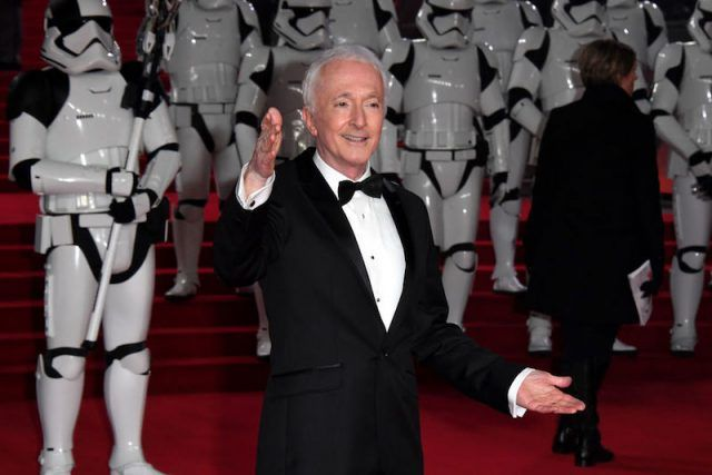 Anthony Daniels posing on a red carpet in front of Storm Troopers.