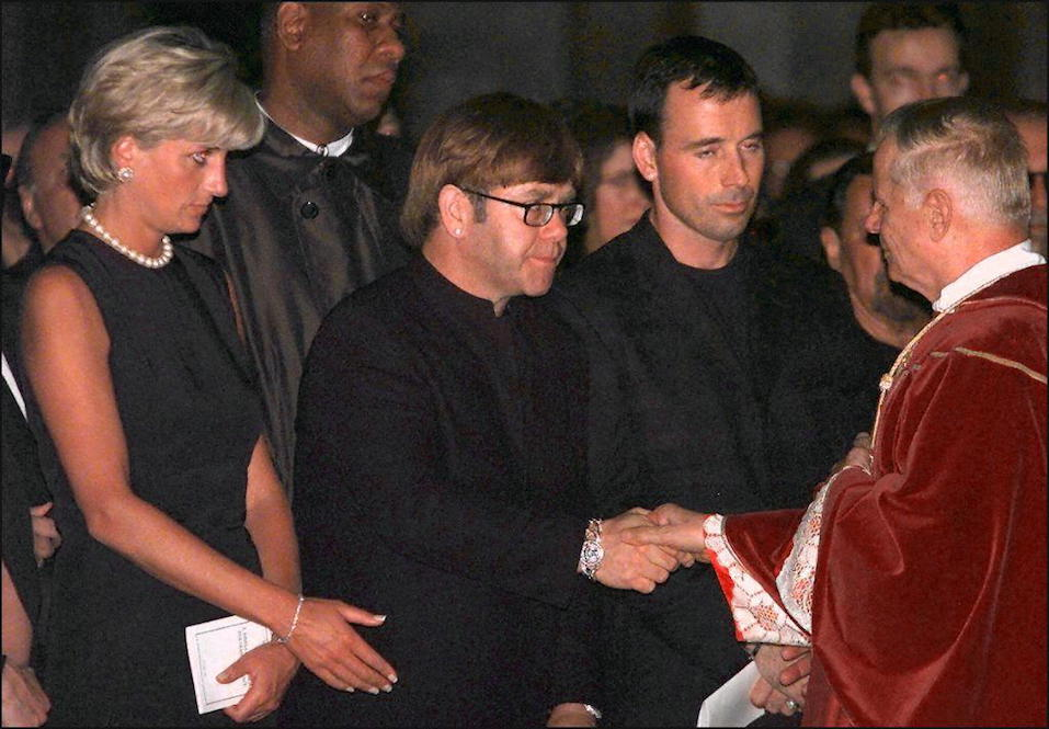 Archpriest Magio (R) shakes hands with British rock star Elton John standing next to Princess Diana (L) during the requiem mass for Italian fashion designer Gianni Versace