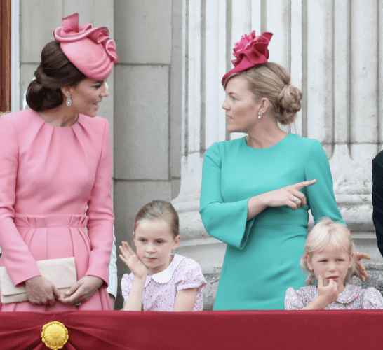 Kate Middleton and Autumn Phillips stand at a balcony.