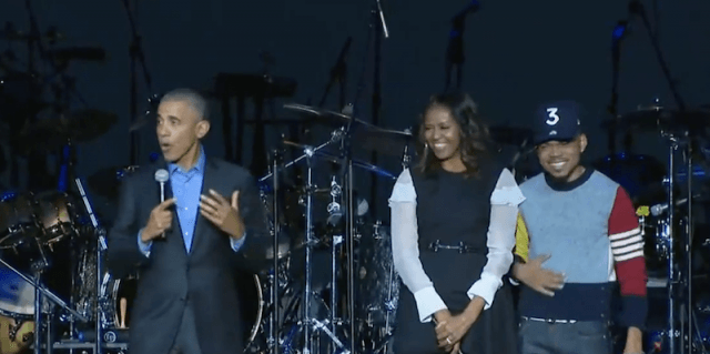 Barack Obama makes a speech while standing next to Michelle Obama and Chance the Rapper.
