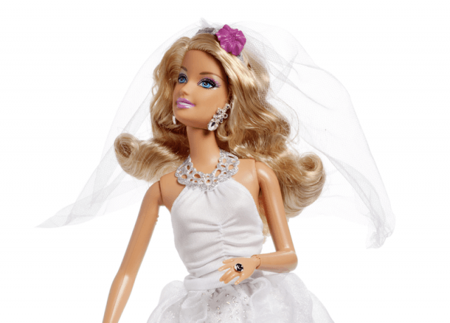 A barbie doll dressed in a white wedding gown.