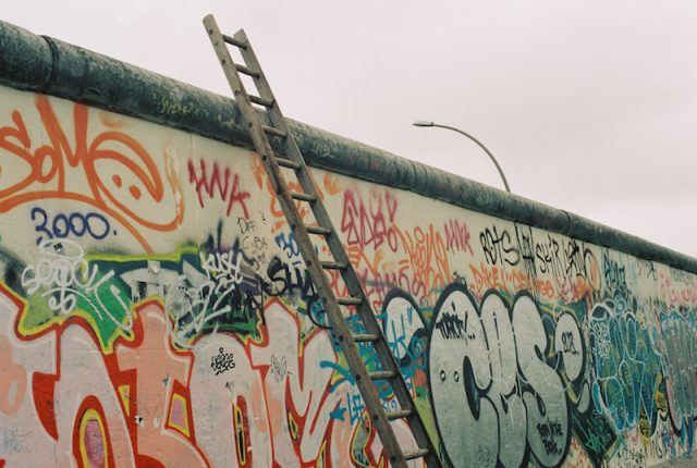 The Berlin Wall seen with a ladder laid on it.