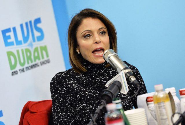 Bethenny Frankel speaking in front of a microphone while wearing a black sweater.