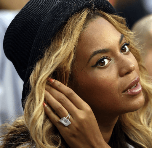 Beyonce adjusting her hair with her left hand at a basketball game.