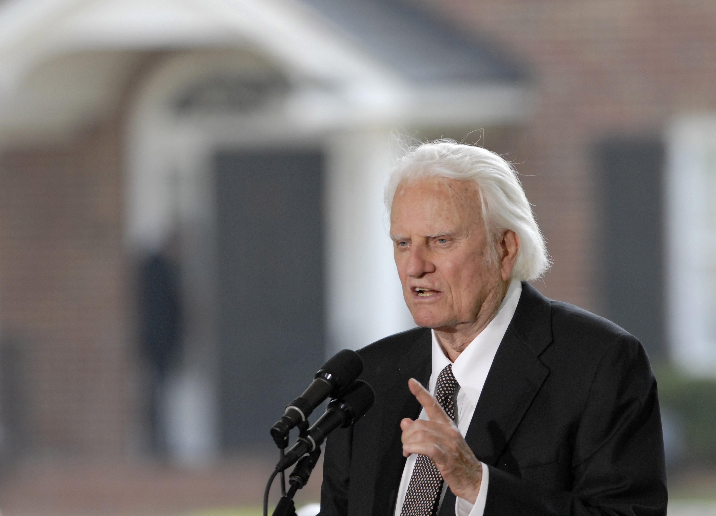 Evangelist Billy Graham speaks into microphone