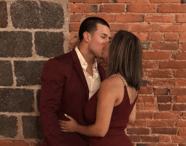 Marroquin and DeJesus kissing in front of a brick wall.