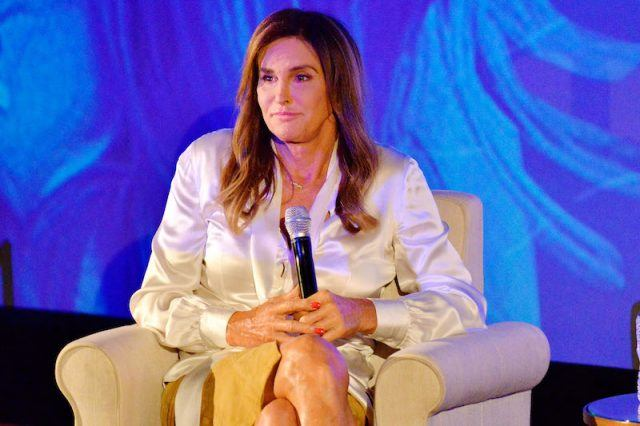 Caitlyn Jenner sitting on a white couch holding a microphone.