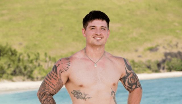 Caleb smiles while standing in front of the island.
