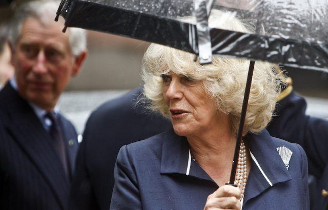 Camilla Parker holds an umbrella.