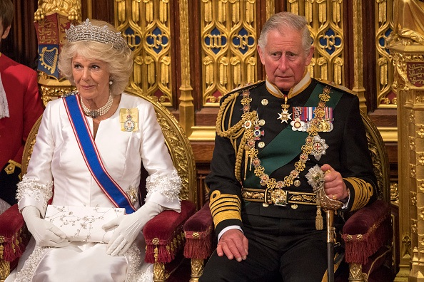 Prince Charles and Camilla sit in gold chairs.