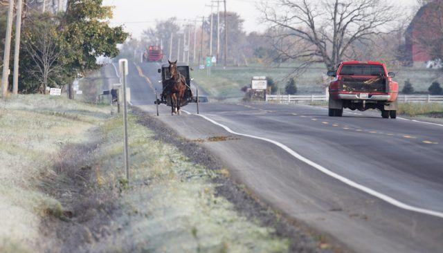 A horse seen pulling a carriage down a street road.