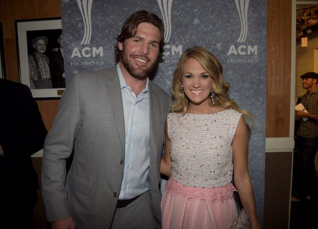 Mike Fisher and Carrie Underwood smile and pose together while holding each other.