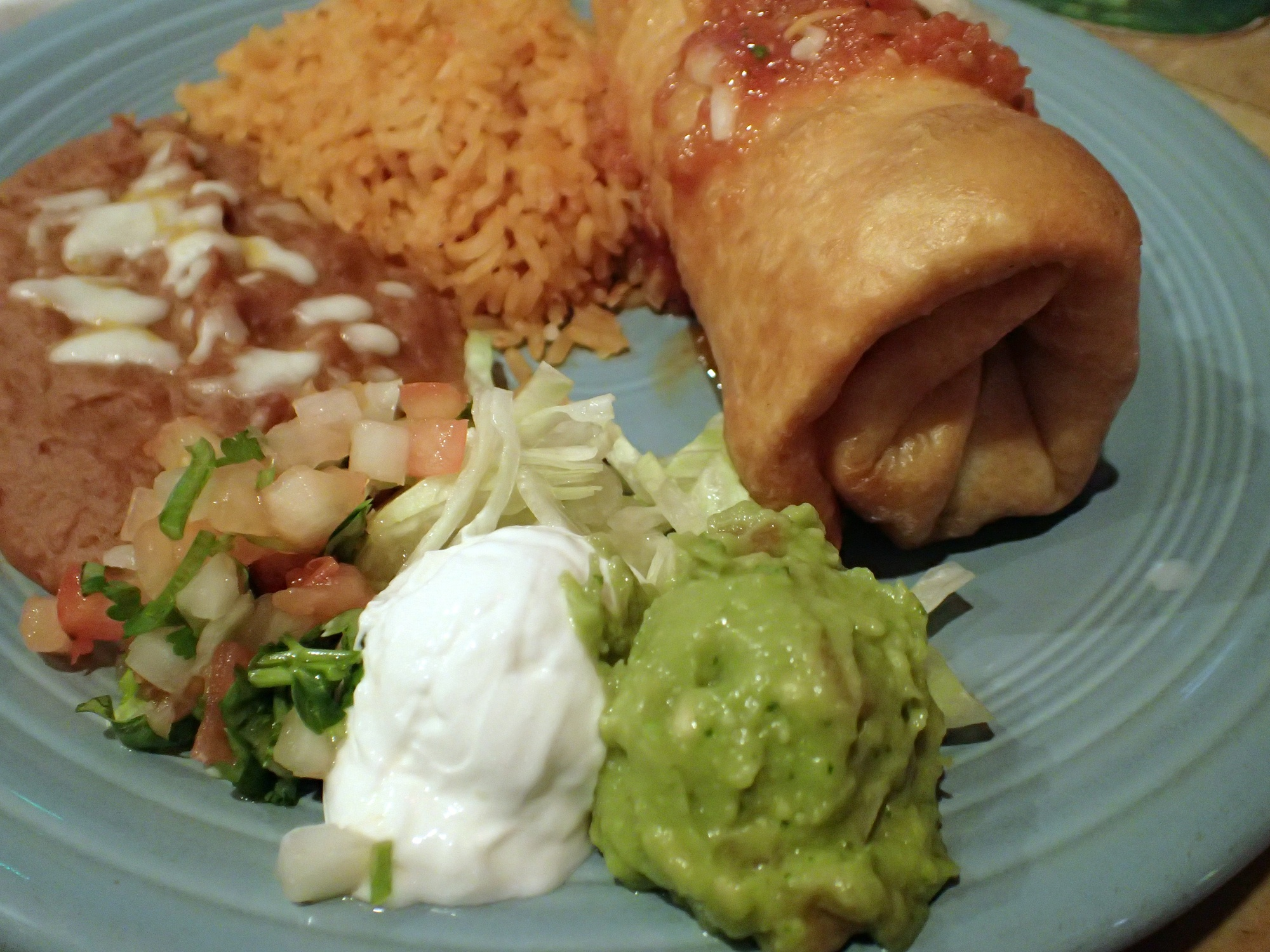 mexican chimichanga plate featuring spanish rice, refried beans, guacamole, pico de gallo, and sour cream on a blue plate