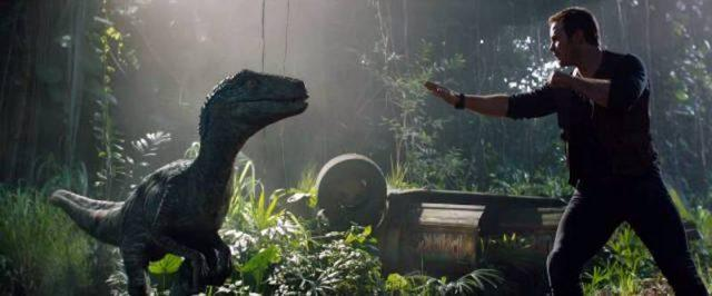 Owen lifts his arms in front of a dinosaur.