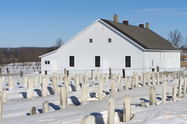 A row of graves in front of a church.
