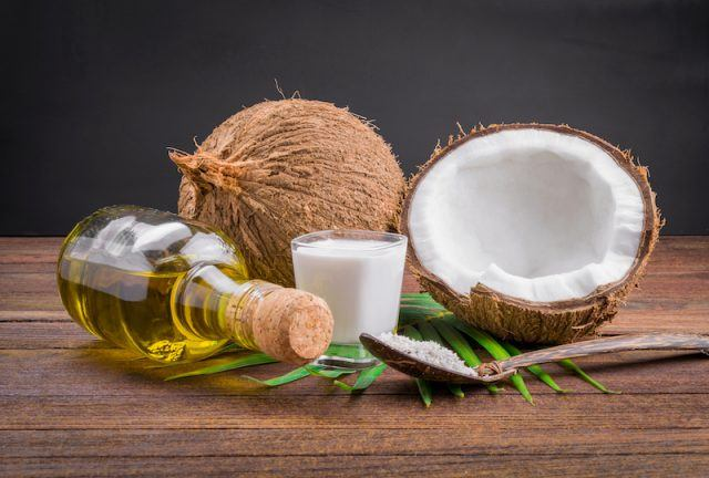 Vinegar and coconuts on a wooden table.