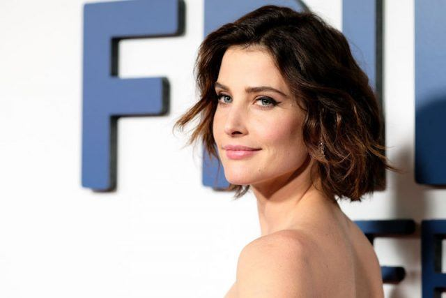 Cobie Smulders posing on a red carpet in a strapless dress.