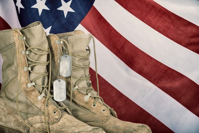 Combat boots and dog tags in front of an American flag.
