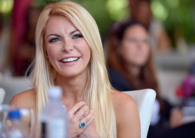 Crystal Hefner sitting at a luncheon.