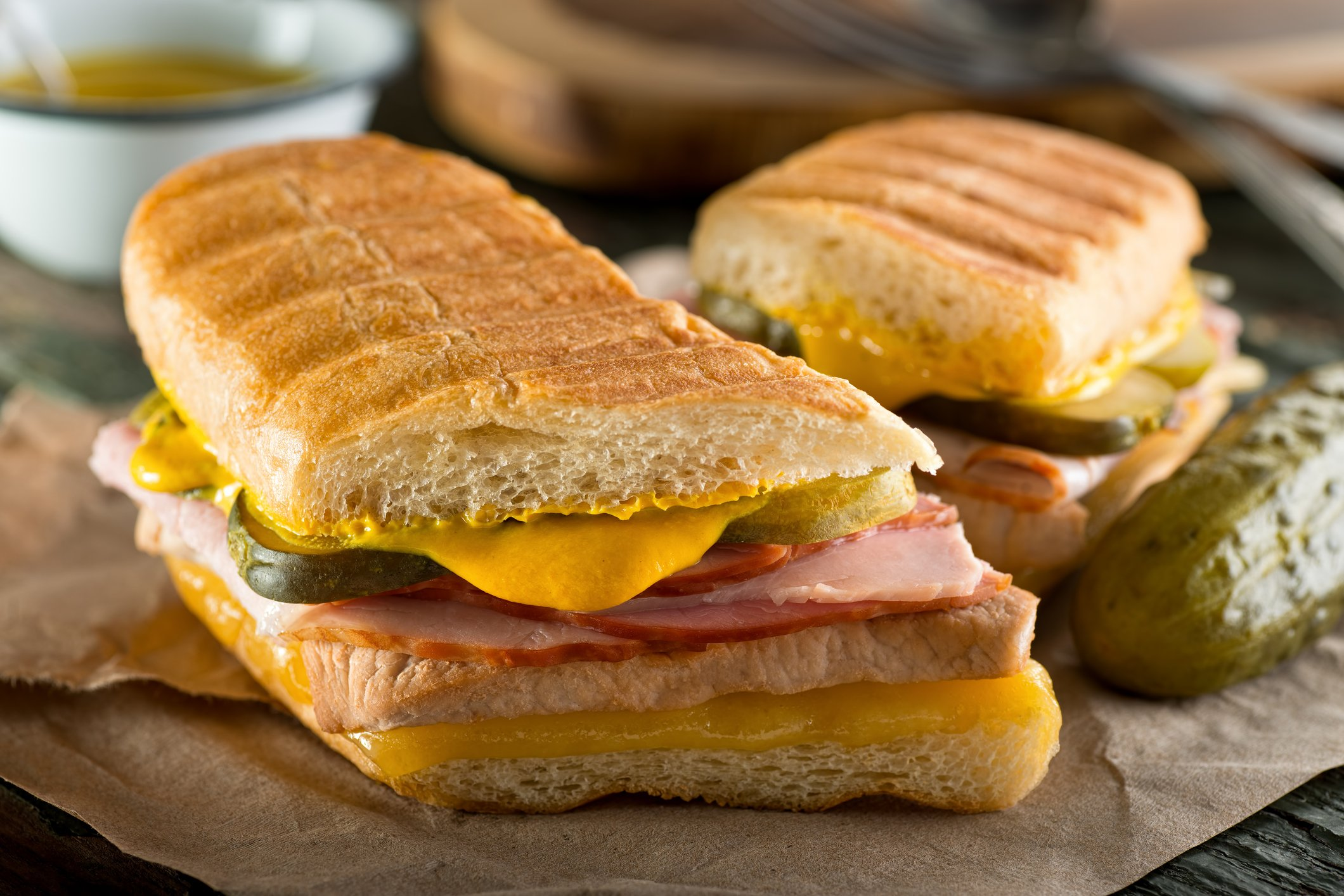 An authentic cuban sandwich on pressed medianoche bread with pork, ham, cheese, pickle, and mustard.