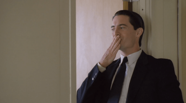 Dale Cooper stands with his hand over his mouth.