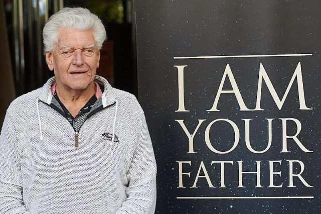 David Prowse posing next to a sign.