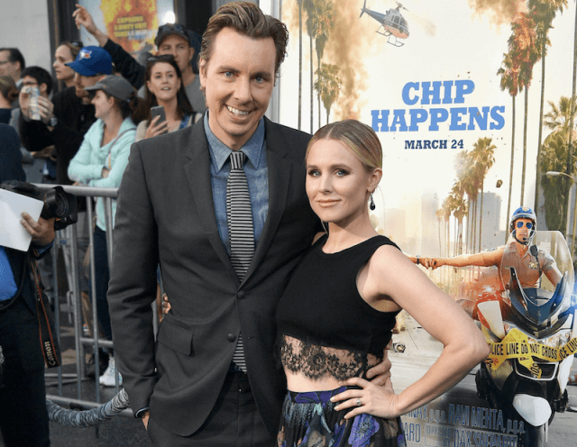 Kirsten Bell poses with Dax Shepard on a red carpet.