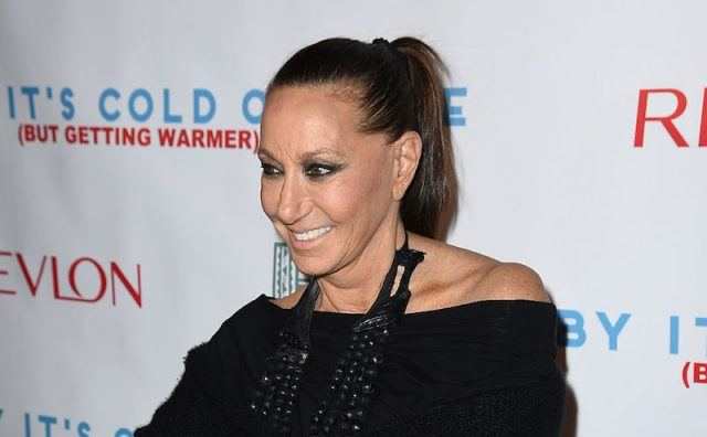 Donna Karan smiling as she poses in a black dress and bead necklace.