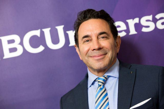Dr. Paul Nassif posing in a suit and tie.