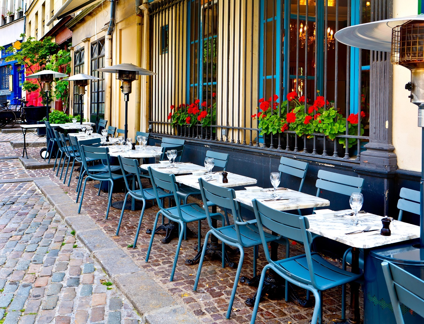 A restaurant cafe in Paris with blue metal chairs and flowers