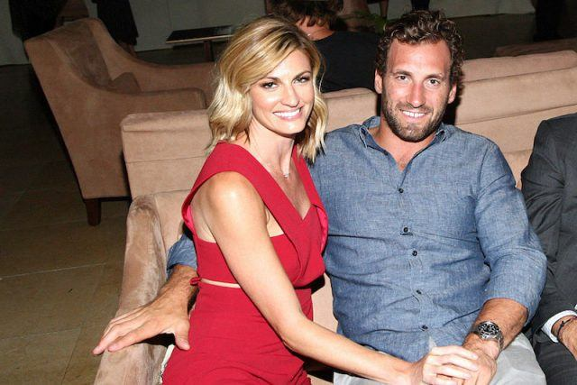 Erin Andrews and  Jarret Stoll sit on a sofa while holding hands.