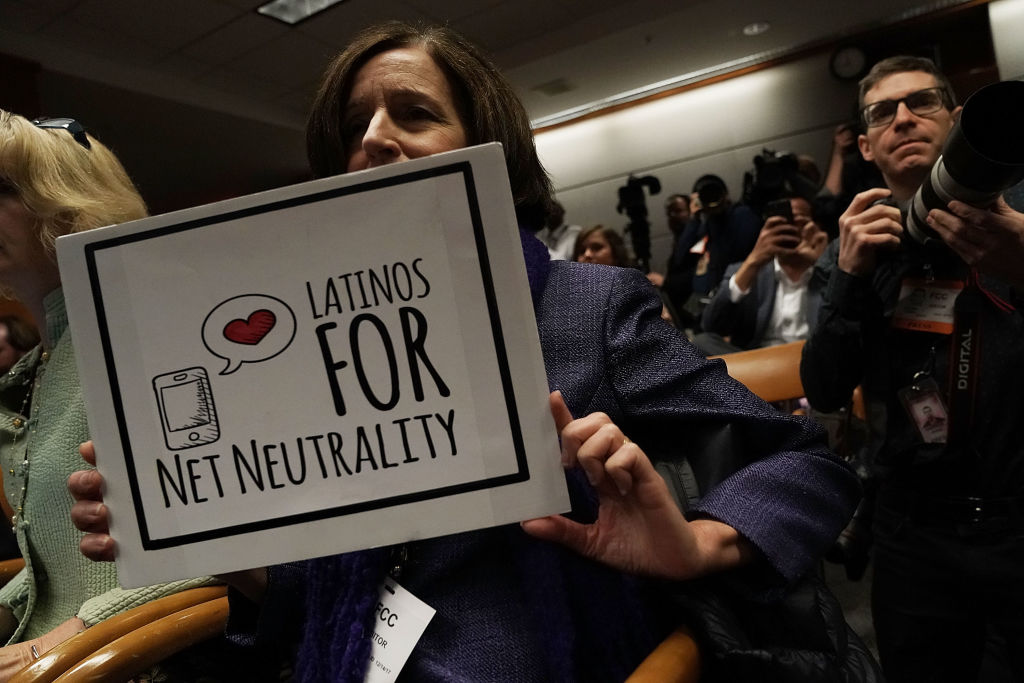 A protester holds a sign during a Federal Communications Commission meeting