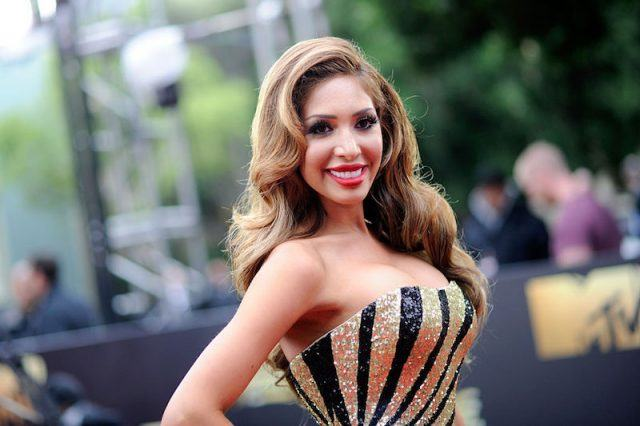 Farrah Abraham posing in a black and gold dress.