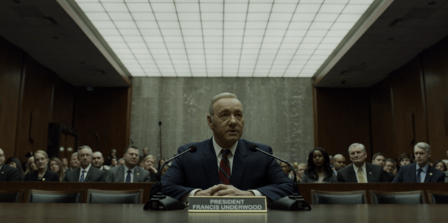 Frank Underwood sits at a desk during an address.