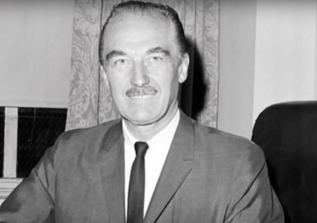 Fred Trump smiling while wearing a suit and tie.
