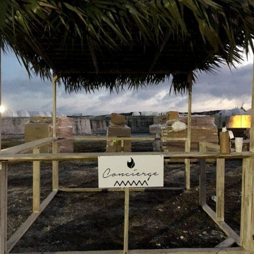 A partially built cabana with a concierge sign attached.