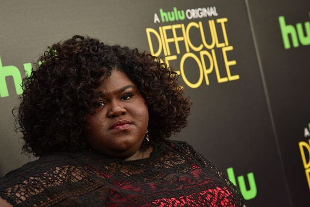 Gabourey Sidibe posing for the paparazzi in a red and black dress.