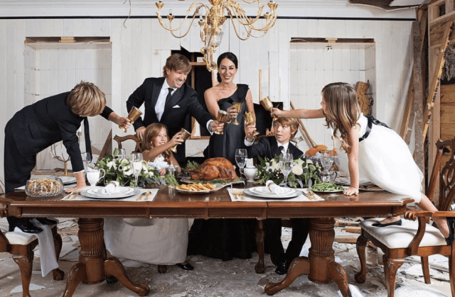 The family toasts together while posing at the dinner table.