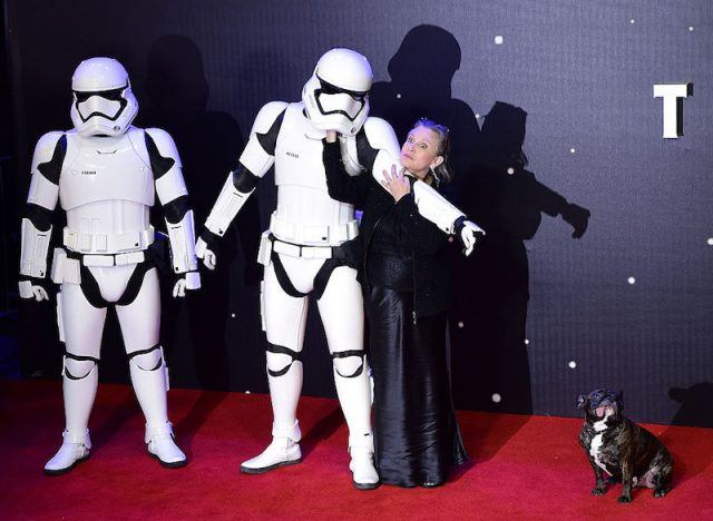 Carrie Fisher holding two storm troopers away from her dog.