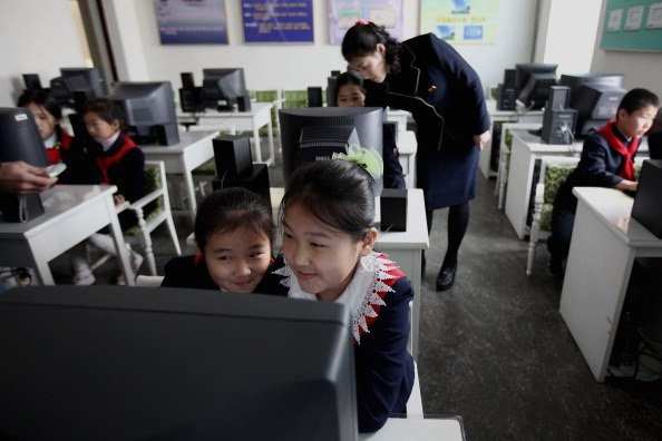 a group of children in uniforms learn to use a computer