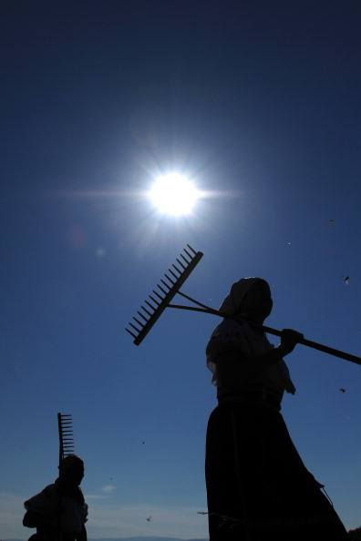 women carrying rakes against a blue sky