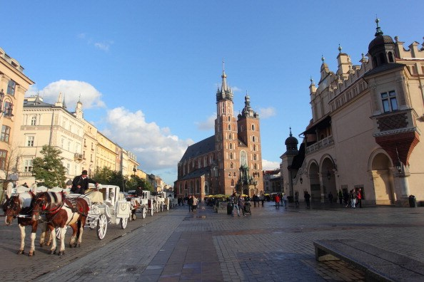 a basilica in the street in poland with a horse-drawn carriage